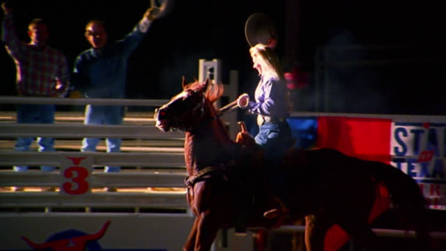 slow motion medium shot tracking shot cowgirl on horseback tipping hat after barrel racing rodeo event - rodeo stock videos & royalty-free footage
