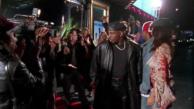Slow motion medium shot tracking shot hip hop couple walking on red carpet between rows of groupies and press