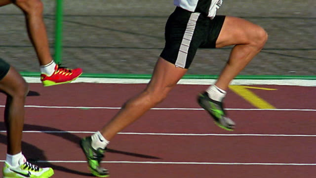 stockvideo's en b-roll-footage met slow motion medium shot tracking shot runners' legs during race / one runner breaking away - elasthaan