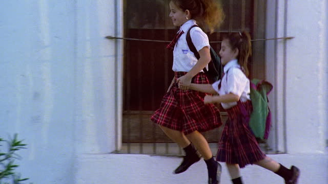 Slow motion medium shot tracking shot two young girls in school uniforms holding hands and skipping on sidewalk