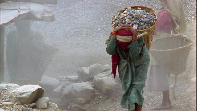 slow motion medium shot tracking shot woman carrying large basket full of rocks on her back / nepal - entwicklungsland stock-videos und b-roll-filmmaterial