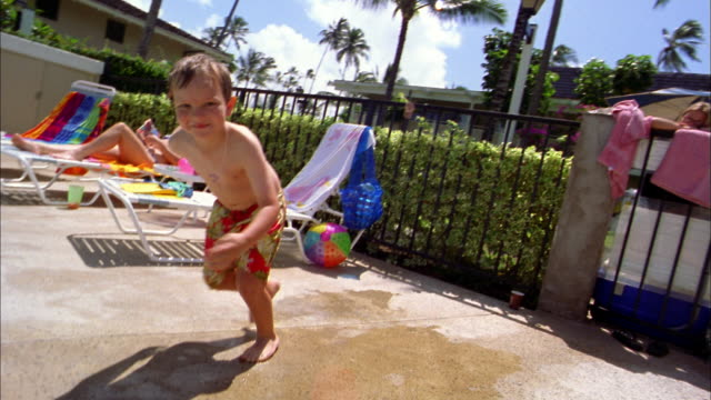 Slow motion medium shot tracking shot young boy jumping into swimming pool and smiling at CAM
