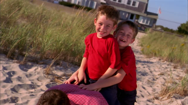 Slow motion medium shot twin boys riding on father's back and falling off at beach