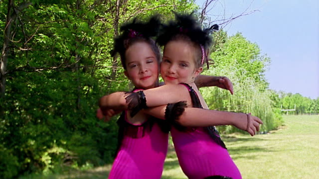 Slow motion medium shot twin girls in costumes / hugging / forest in background