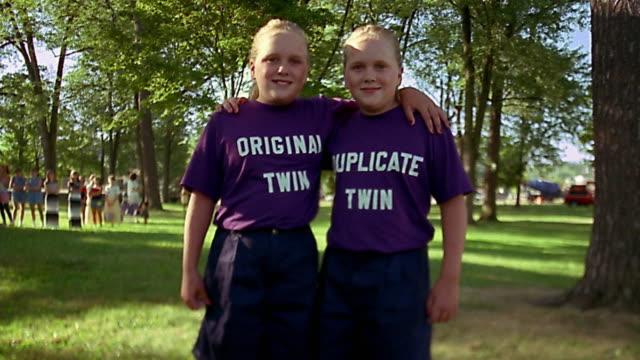 Slow motion medium shot twin girls in purple T shirts