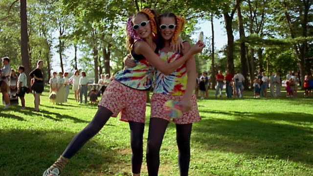 Slow motion medium shot twin teenage girls in wacky costumes with sunglasses posing and hugging