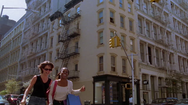 Slow motion medium shot two young women laughing while walking down street with shopping bags / Soho, NYC