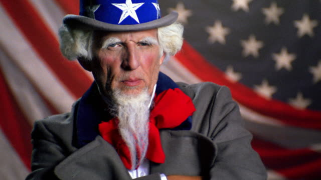 slow motion medium shot uncle sam posing with arms folded in front of american flag - uncle sam stock videos & royalty-free footage
