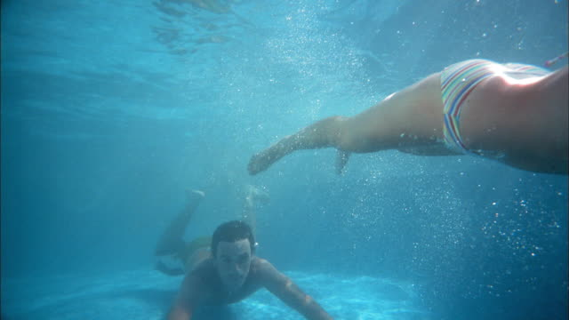 Slow motion medium shot woman and man swimming underwater / man smiling at CAM