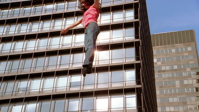 Slow motion medium shot woman bouncing in air against building / flipping in air