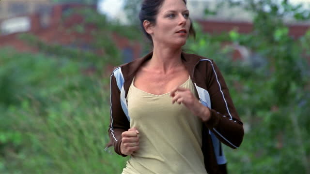 Slow motion medium shot woman jogging past CAM / Milwaukee, Wisconsin