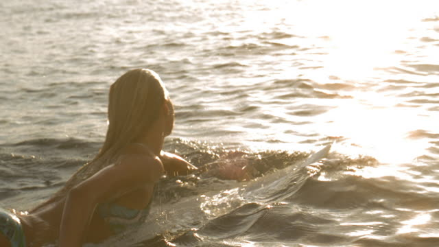 Slow motion medium shot woman paddling through shallow water face down on surfboard / Tahiti