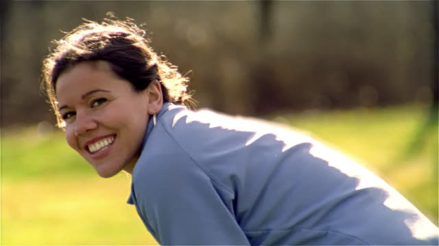 slow motion medium shot woman smiling/ tracking shot football being caught by woman in touch football game/ maine - touch football stock videos & royalty-free footage