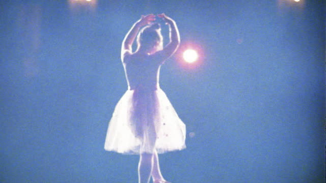 Slow motion medium shot young ballerina bowing and walking away with bright light in background