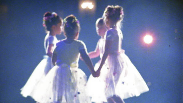 Slow motion medium shot young ballerinas in tutus holding hands and circling w/confetti falling / spinning alone