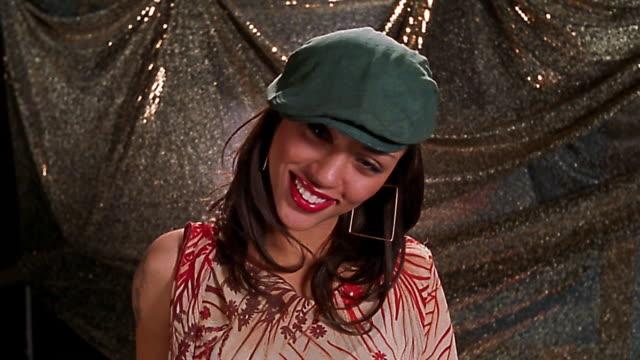 Slow motion medium shot young Black woman wearing cap and asymetrical blouse laughing + posing / walking away