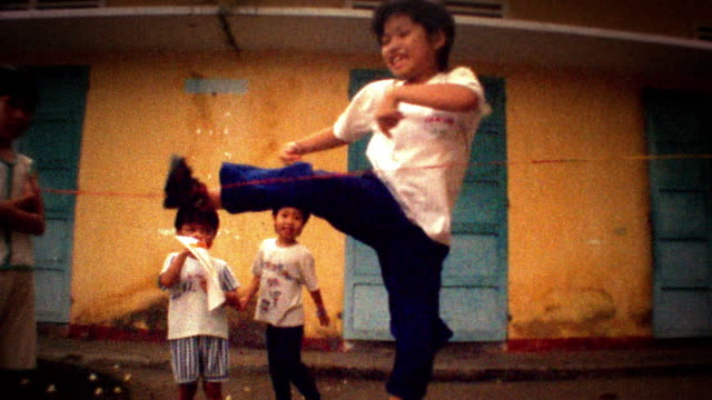 Slow motion medium shot young boy smiling and jumping over thin rope with other children in background / Vietnam