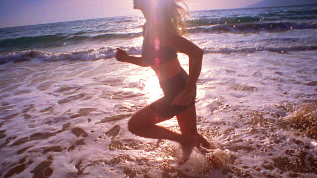 slow motion medium shot young woman running on beach and jumping with arms extended in shallow surf / maui, hawaii - spandex stock videos & royalty-free footage