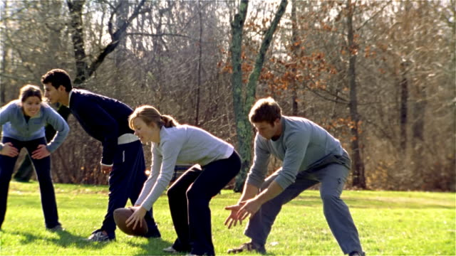 slow motion medium tracking shot pan men and women playing football/ maine - tracksuit bottoms stock videos & royalty-free footage