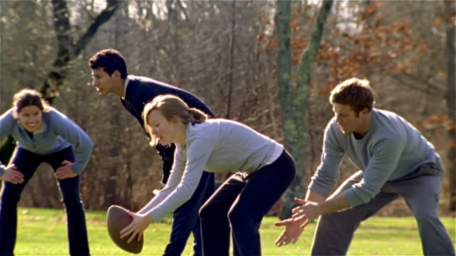 Slow motion medium tracking shot pan men and women playing football/ Maine