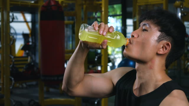 4k slow motion men exercising in professional gym he is drinking mineral water. after exercising in the gym - lap body area stock videos & royalty-free footage