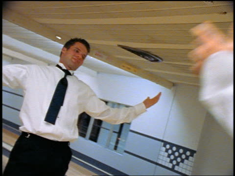 stockvideo's en b-roll-footage met slow motion men in formalwear goofing around in bowling alley - compleet pak