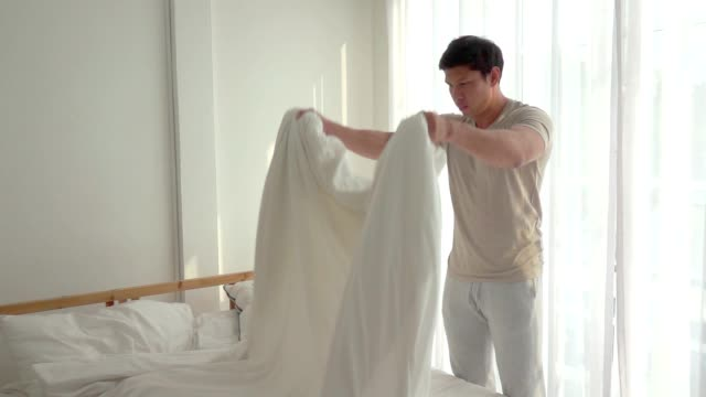 slow motion men making a bed - duvet stock videos & royalty-free footage