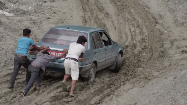 nepal - august 1, 2015: slow motion men push blue car on muddy road - bloccato video stock e b–roll