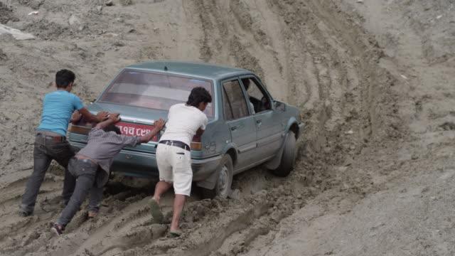 stockvideo's en b-roll-footage met nepal - august 1, 2015: slow motion men push blue car on muddy road - klem