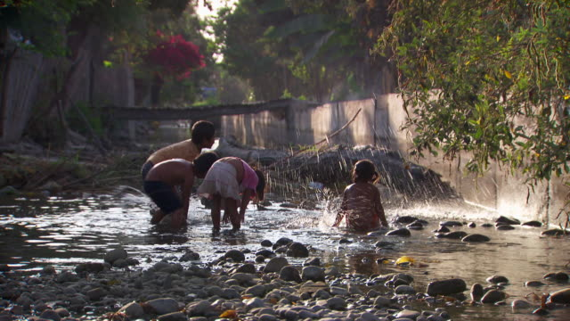 """slow motion mid of young children splashing water up in the air, bright sunlight lighting up the droplets, rural villiage, leimebamba [leymebamba] valley, peru"" - nur kinder stock-videos und b-roll-filmmaterial"