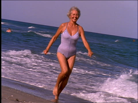 vidéos et rushes de slow motion middle aged woman in swimsuit running on beach - maillot une pièce