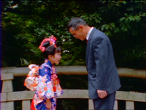 slow motion middle-aged japanese man + girl in kimono bowing to each other outdoors / japan - respect stock videos and b-roll footage