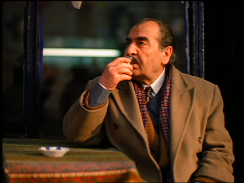 slow motion middle-aged turkish businessman sitting at table outdoors drinking tea from glass / istanbul - moustache stock videos & royalty-free footage