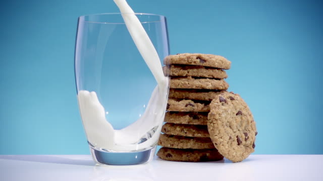 slow motion milk pouring into glass with cookies - chocolate milk stock videos & royalty-free footage