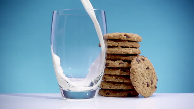 slow motion milk pouring into glass with cookies - chocolate chip cookie stock videos and b-roll footage