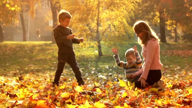 slow motion: mother and children in the park - leaf stock videos & royalty-free footage