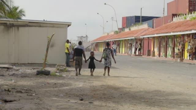 slow motion: mother, father, daughter hold hands walking away from camera - haiti stock videos & royalty-free footage