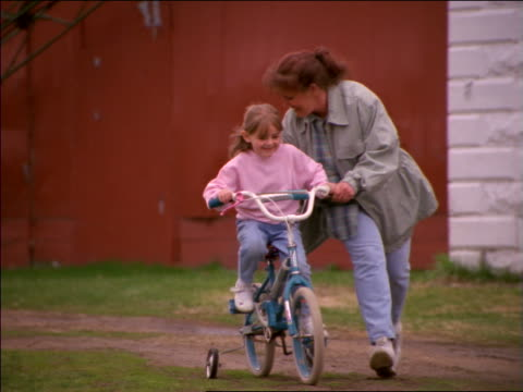 vídeos de stock e filmes b-roll de slow motion pan mother helping daughter learn to ride bike with training wheels as girl runs behind them - família com dois filhos