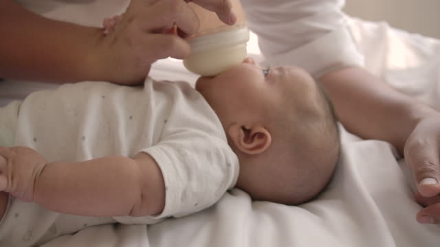 slow motion mother is breastfeeding from a bottle. - biberon video stock e b–roll