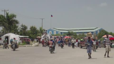 slow motion: motorbikes cruise away, those with supplies walk toward camera - ハイチ点の映像素材/bロール