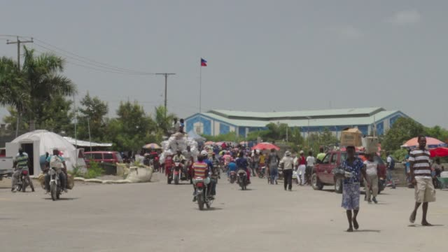slow motion: motorbikes cruise away, those with supplies walk toward camera - haiti stock videos & royalty-free footage