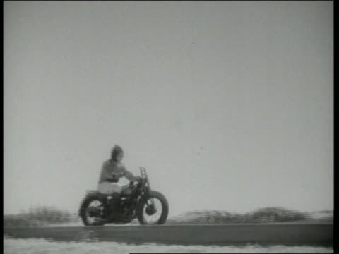 b/w 1943 slow motion pan motorcyclist jumping through wall of flames / hollywood daredevils - stunt stock videos & royalty-free footage