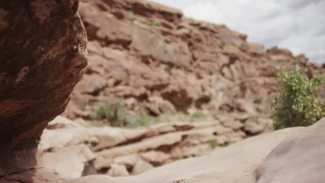 Slow motion, mountain bikers jump over rocks in Utah canyon