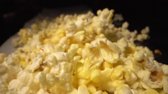 スローモーション移動カメラ広角は、カウンタートップに新鮮なバター脂っこい黄色のポップコーンのヒープの移動ショット - 塩味スナック点の映像素材/bロール