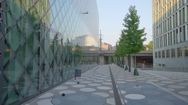 slow motion moving forward through the modern and abstract concrete courtyard of the berlin futurium, with small trees and soaring glass-sided buildings - berlin stock videos & royalty-free footage