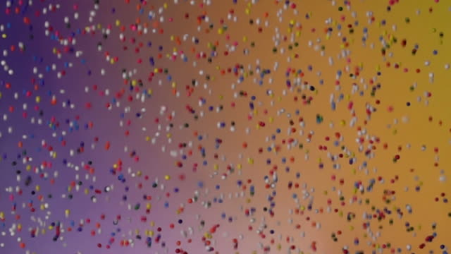 slow motion: multi color grain falling and bouncing on gradient color bg - sprinkles stock videos & royalty-free footage
