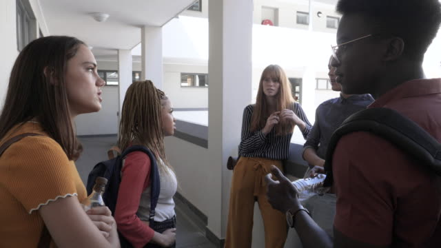 slow motion, multi ethnic group of college students talk outside class - community college stock videos & royalty-free footage