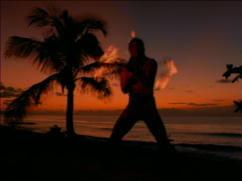 vídeos y material grabado en eventos de stock de slow motion native man dancing with flaming torch on beach at sunset / hawaii - 1997