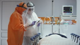Slow Motion: Nurse in a Protective Suit Measuring Coronavirus Patient's Temperature and Consulting with Leading Doctor - Wide Dolly Shot. Shot in 5K R3D