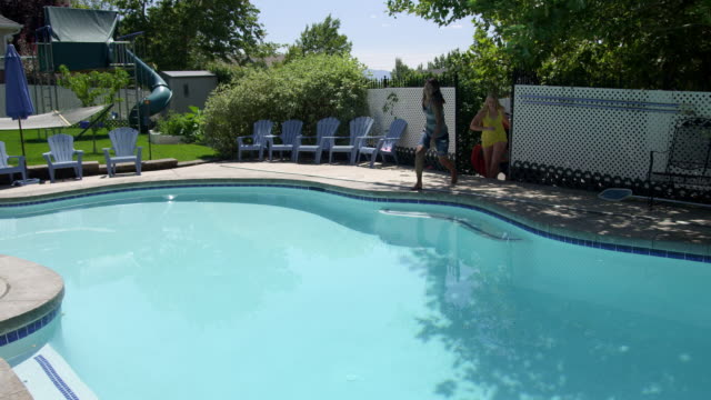 vídeos de stock, filmes e b-roll de slow motion of 3 girls coming through gate and jumping into swimming pool. - sem manga